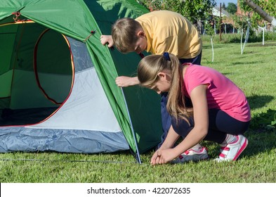 a boy with a girl pitch a tent