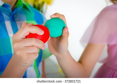 The boy and  girl are playing colored Easter eggs