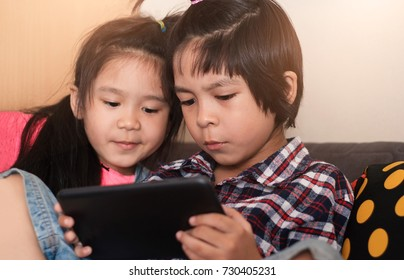 Boy and girl playing digital tablet while sitting on sofa at home