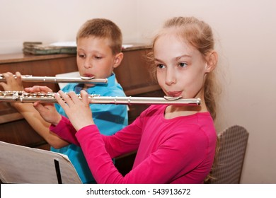 a boy and a girl playing the flute in the music room