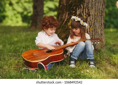 boy and girl playing guitar in summer park