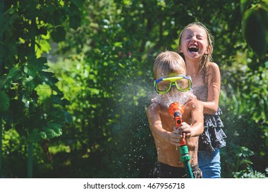 Boy with a girl playing in the hot summer, spraying each other with water from a garden hose.Toning.Focus on boy