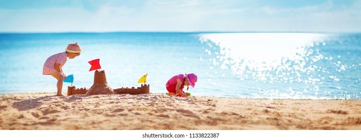 Boy and girl playing on the beach on summer holidays. Children building a sandcastle at sea