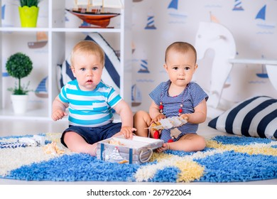 boy and girl playing on the floor with seashells