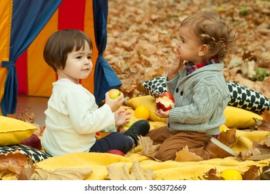 Boy and girl playing in the park and eating apple.Autumn leaves in the background