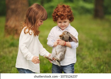 boy and girl playing with rabbit in park