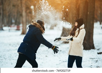 boy and girl playing with snow in snow-covered park