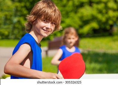 Boy and girl playing together ping pong outside