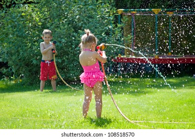 Boy and girl playing with water hoses in the garden