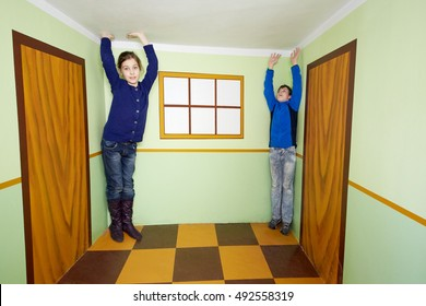 Boy and girl pose in room with optical illusion.