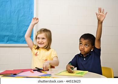Boy and Girl raising hands in art class. Horizontally framed shot.