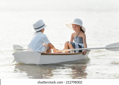 Boy with a girl riding on a boat on the lake in summer sunny day