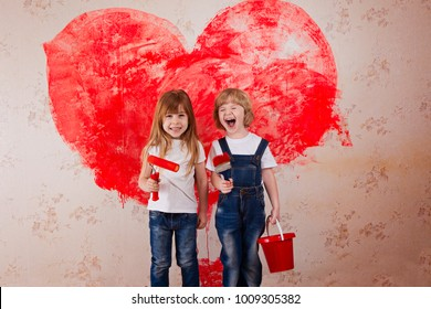 a boy and a girl with a roller in jeans and a white T-shirt, a brush and a bucket paint the wall in red. big painting heart