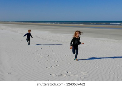 Boy and girl running on a white sand beach in Florida, USA