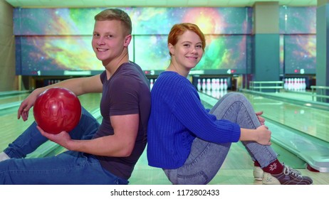 Boy and girl show their thumbs up at the bowling