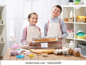 Boy and girl shows a tray of baked cookies, home kitchen interior, homemade food concept