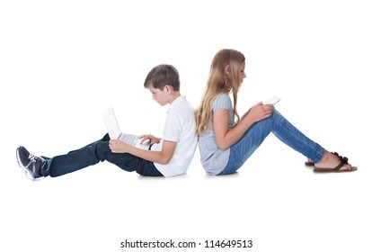 Boy And Girl Sitting Back To Back Using Laptop And Digital Tablet Isolated On White Background