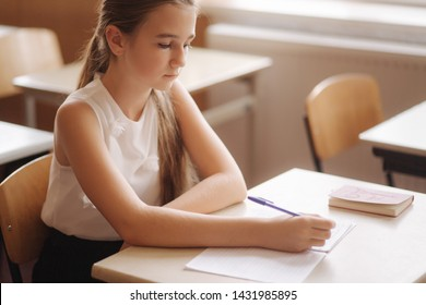 Boy and girl sitting at desk and writing a text
