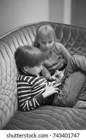 Boy and girl sitting on the couch watching the computer screen