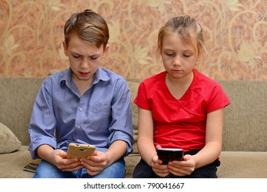 Boy and girl sitting on the couch with phone