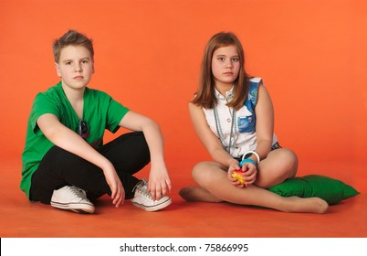 Boy and girl sitting on the floor. Orange background
