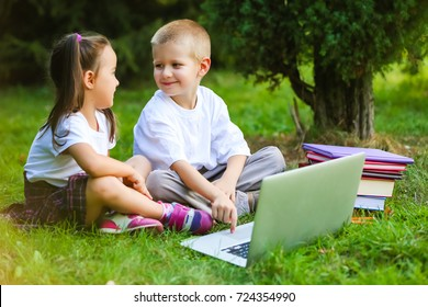 Boy and girl sitting on grass with laptop, online in park. Two smiling students with laptop resting on meadow. Education. Technology.