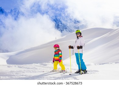 Boy and girl skiing in mountains. Toddler kid and teenager with helmet, goggles, poles. Ski race for children. Winter sport for family. Kids ski lesson in alpine school. Little skier racing in snow