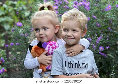 Boy and girl stand embracing against the background of flowers