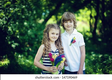 a boy and a girl standing in the park, in the hands of the girl flowers (hyacinth) smiles