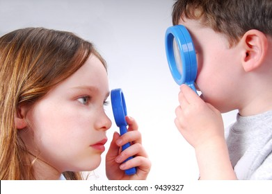 Boy and Girl Studying One Another with Magnifying Glasses