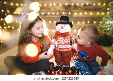 boy and girl in sweaters playing with snowman at christmas studio