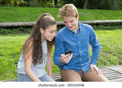 Boy and girl , teen looking at a smartphone
