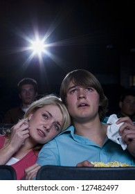 Boy and girl with tissues crying at movie theater