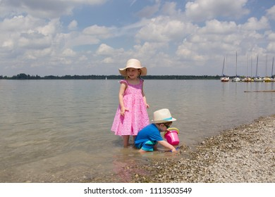 A boy and a girl in toddlerhood are standing on a log in summer clothes, looking to the left