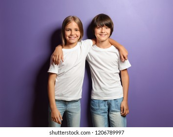 Boy and girl in t-shirts hugging each other on color background