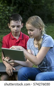 Boy and girl of twelve years in nature with iPads.