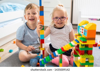 A boy and girl twins are playing with blocks in their room