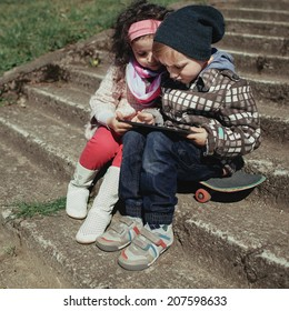 boy and girl using tablet together outdoors