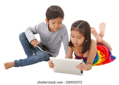 Boy and girl using tablet while lying on the floor