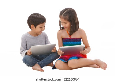 Boy and girl using tablet while sitting on the floor