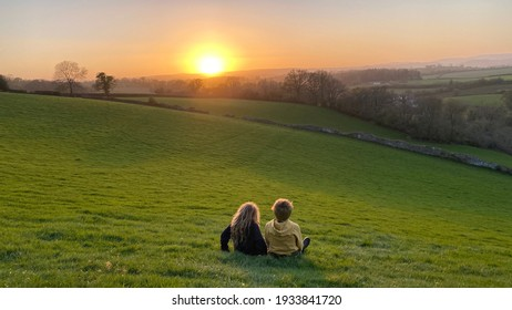 Boy and girl watching sunset over Devon fields.