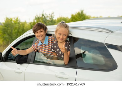 Boy and girl waves from car window. Happy children travels with his parents by car.