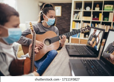 Boy and girl, wear protective masks, playing acoustic guitar and watching online course on laptop while practicing at home. Online training, online classes.