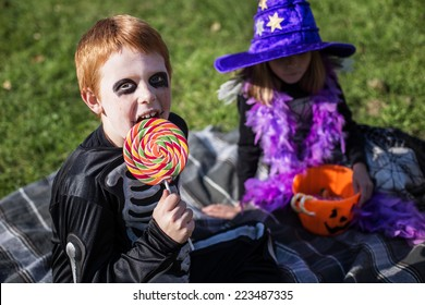 boy and girl wearing halloween costume with candies witch skeleton outdoor portrait