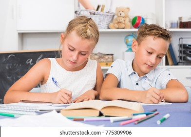 Boy with girl are writing in notebook their homework at home.