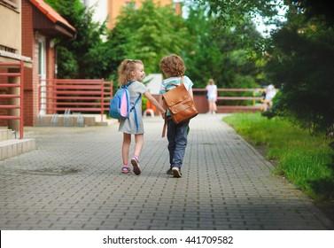 Junge und Mädchen gehen zur Schule, nachdem sie sich den Händen angeschlossen haben. Warmer September-Tag. Gute Laune. Hinter dem Rücken auf die Kinder sitzen. Das Mädchen lacht. Zurück zur Schule.  Kleiner erster Grader.