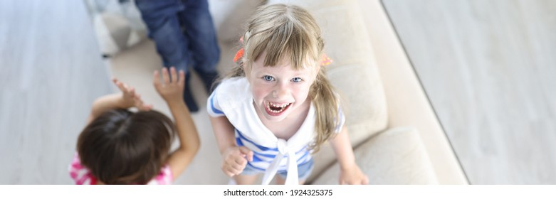 Boy and girls laugh and jump on couch at home. Home games for children concept