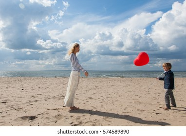 boy gives a balloon in the shape of a heart to his mother on Valentine's Day