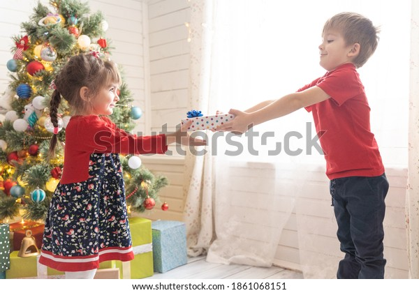 Boy gives Christmas present to girl at social distance due to pandemic COVID-19.