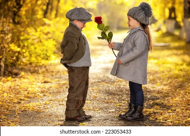 Boy gives a flower girl walking down the avenue in the park autumn day